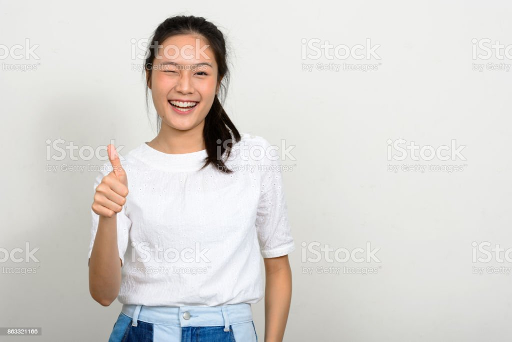 Young beautiful Asian woman with long straight hair wearing white shirt against white background stock photo