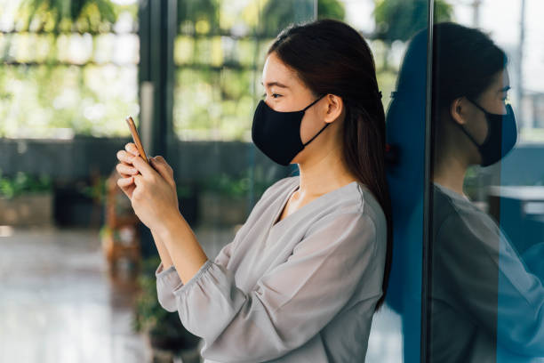 Young beautiful Asian woman with surgical mask for face protection using a smartphone at office building. stock photo