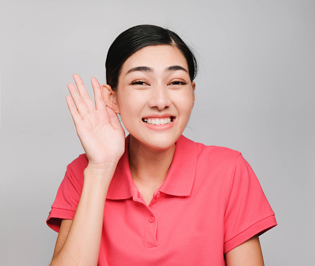 Young Beautiful Asian Woman Wore Pink T Shirt Showed Listen Expression On Gray Background Stock Photo - Download Image Now