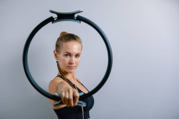 Young, beautiful, athletic girl is doing exercises with the Pilates ring in the gym on a gray background. Sporting Slavic girl in a blue, green suit. Copy space, gray background, sport banner for advertising stock photo