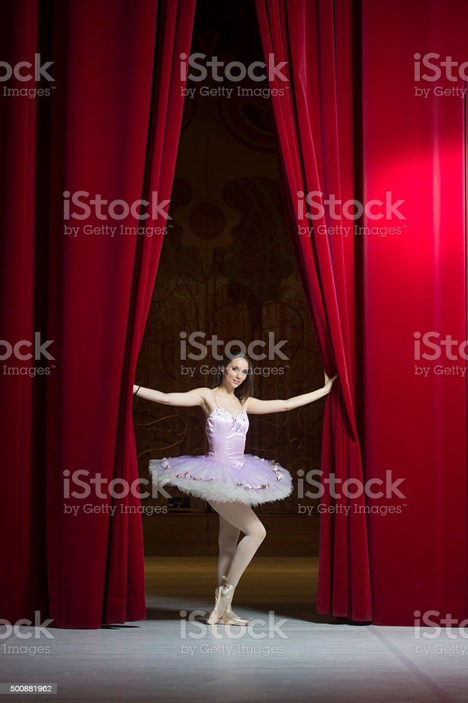 Young beautiful ballerina posing in front of red stage curtain stock photo