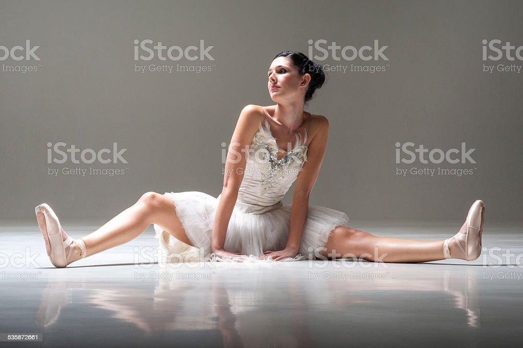Young beautiful ballerina strecthing legs on studio floor stock photo