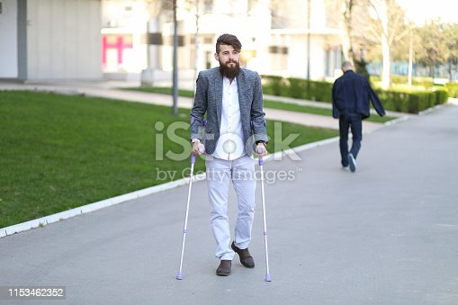 Young beautiful bearded man with walking sticks on the street. Outdoor environment