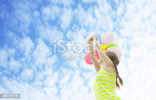 istock Young Beautiful birthday girl with colorful baloons on clouds 467107751