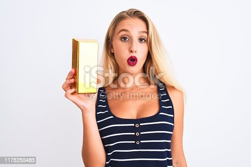 Young beautiful blond woman holding gold ingot standing over isolated white background scared in shock with a surprise face, afraid and excited with fear expression