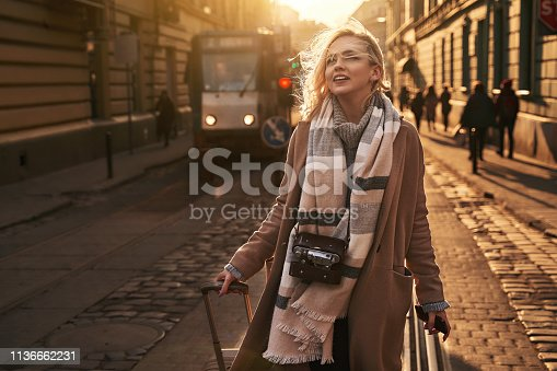 Young beautiful blond woman tourist with a wheeled travel bag and vintage film camera arrives to a new city on a sunny windy evening at golden hour.