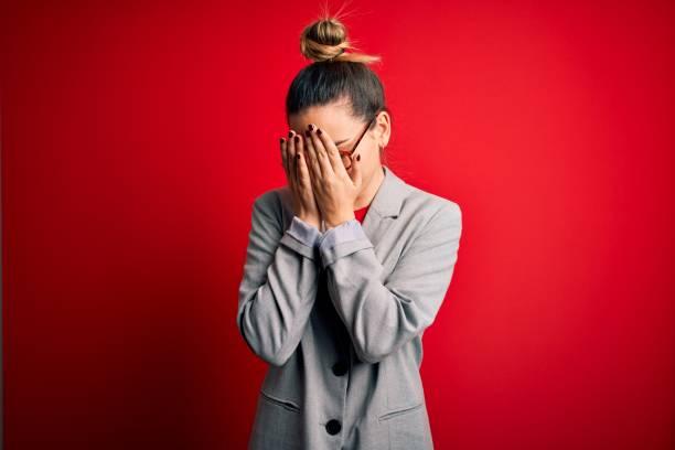 joven hermosa mujer de negocios rubia con ojos azules con gafas y chaqueta con expresión triste cubriendo la cara con las manos mientras llora. concepto de depresión. - vergüenza fotografías e imágenes de stock