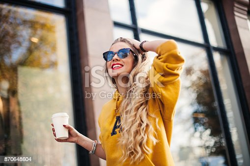 870648602 istock photo young beautiful blonde drinking coffee walking around the city.mustard sweetshot.,urban backpack , bright red lips Posing against the window of the boutique 870648604