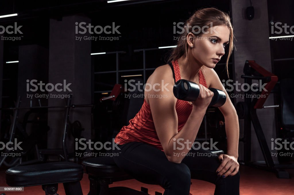 Young beautiful blonde girl is engaged in sports training with dumbbells in the gym. Portrait stock photo