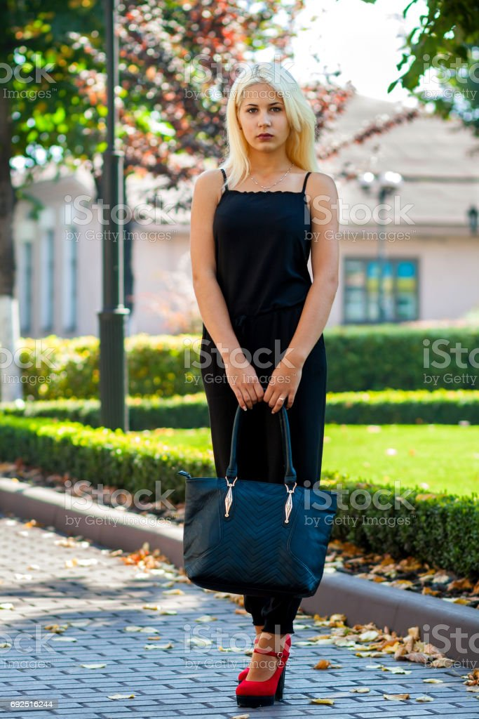 Young Beautiful Blonde Girl Posing On The Background Of The Urban