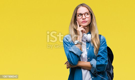 Young beautiful blonde student woman wearing headphones and glasses over isolated background with hand on chin thinking about question, pensive expression. Smiling with thoughtful face. Doubt concept.