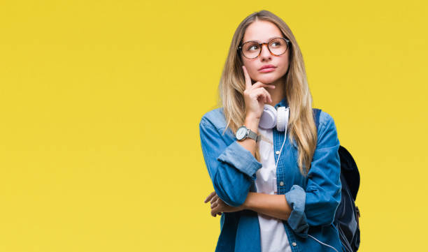 young beautiful blonde student woman wearing headphones and glasses over isolated background with hand on chin thinking about question, pensive expression. smiling with thoughtful face. doubt concept. - stupidblonde stock pictures, royalty-free photos & images