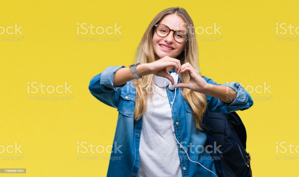 Young beautiful blonde student woman wearing headphones and glasses over isolated background smiling in love showing heart symbol and shape with hands. Romantic concept. stock photo