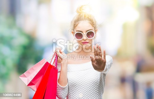 Young beautiful blonde woman holding shopping bags over isolated background with open hand doing stop sign with serious and confident expression, defense gesture
