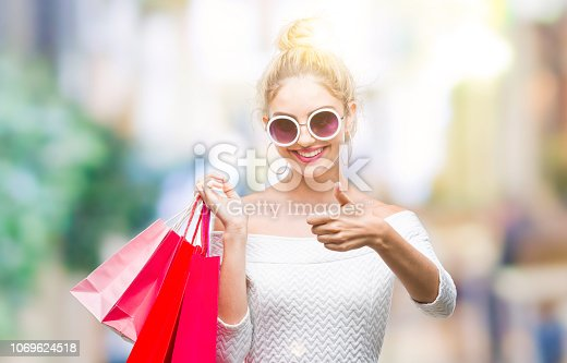 Young beautiful blonde woman holding shopping bags over isolated background happy with big smile doing ok sign, thumb up with fingers, excellent sign