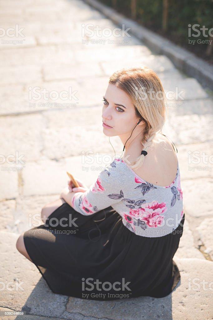 Joven rubia hermosa mujer escucha música al aire libre foto de stock libre de derechos