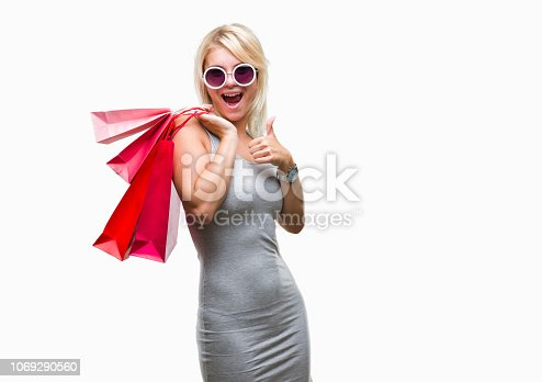 Young beautiful blonde woman shopping holding shopping bags on sales over isolated background happy with big smile doing ok sign, thumb up with fingers, excellent sign