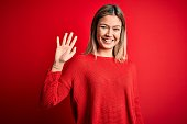 Young beautiful blonde woman wearing casual sweater over red isolated background Waiving saying hello happy and smiling, friendly welcome gesture