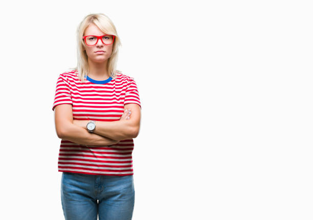 young beautiful blonde woman wearing glasses over isolated background skeptic and nervous, disapproving expression on face with crossed arms. negative person. - frowning stock photos and pictures