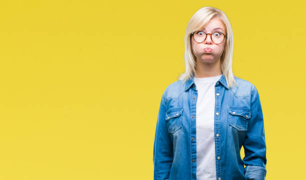 Young beautiful blonde woman wearing glasses over isolated background puffing cheeks with funny face. Mouth inflated with air, crazy expression. Young beautiful blonde woman wearing glasses over isolated background puffing cheeks with funny face. Mouth inflated with air, crazy expression. grimacing stock pictures, royalty-free photos & images