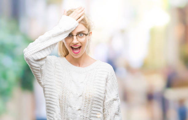young beautiful blonde woman wearing glasses over isolated background surprised with hand on head for mistake, remember error. forgot, bad memory concept. - stupidblonde stock pictures, royalty-free photos & images