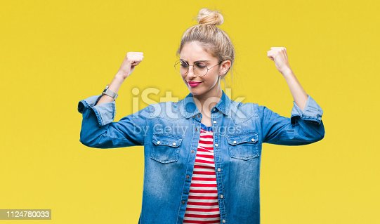 istock Young beautiful blonde woman wearing glasses over isolated background showing arms muscles smiling proud. Fitness concept. 1124780033