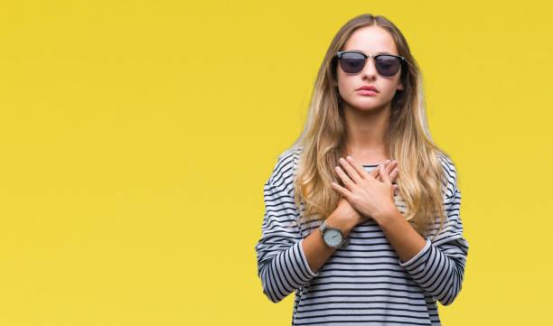 junge schöne blonde frau mit sonnenbrille über isolierte hintergrund lächelnd mit die hände auf die brust mit geschlossenen augen und dankbar geste auf gesicht. gesundheitskonzept. - die wahrheit tut weh stock-fotos und bilder