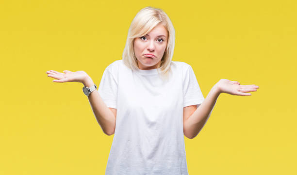 young beautiful blonde woman wearing white t-shirt over isolated background clueless and confused expression with arms and hands raised. doubt concept. - stupidblonde stock pictures, royalty-free photos & images