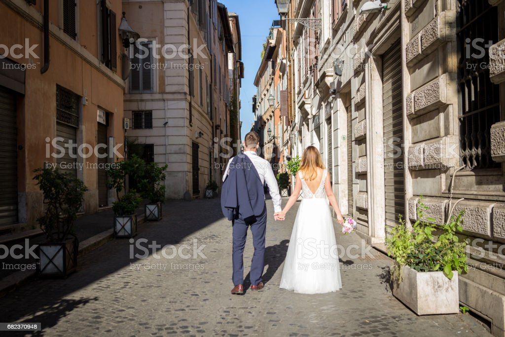 Young beautiful bride and groom on the wedding walk through the streets of old Rome, Italy. foto stock royalty-free