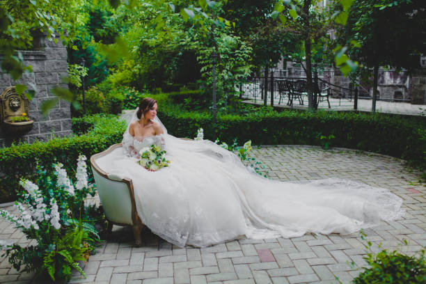 Young beautiful bride in luxury dress with a long train sitting on a sofa stock photo