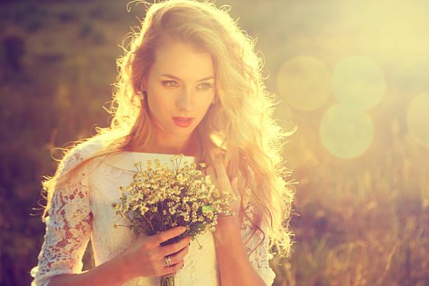 junge schöne braut im freien bei sonnenuntergang - hochzeitsfrisur twilight stock-fotos und bilder