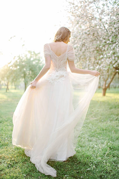 Young beautiful bride portrait in park with flowers stock photo