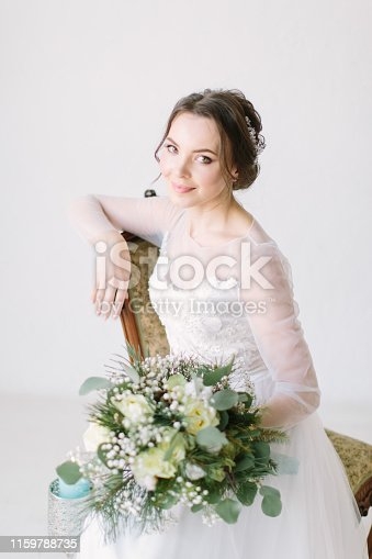 young beautiful bride sitting in a chair and smiling, close-up. Beauty portrait of bride wearing fashion wedding dress with feathers with luxury delight make-up and hairstyle, studio indoor photo.