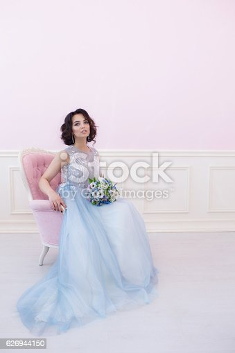 578573556istockphoto Young beautiful bride sitting in a pink chair. 626944150