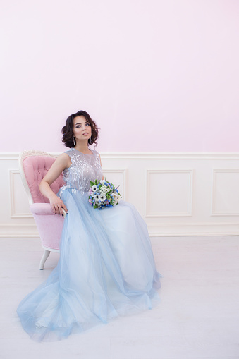 578573556 istock photo Young beautiful bride sitting in a pink chair. 626944150