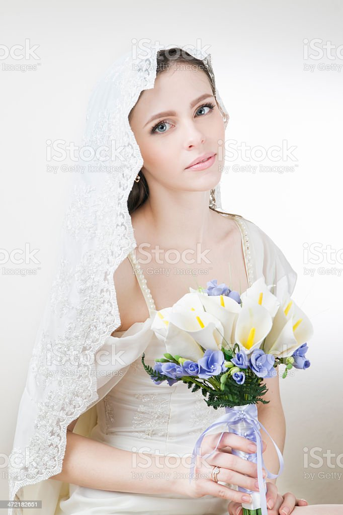 Young beautiful bride with a wedding bouquet stock photo