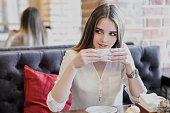 A young beautiful brown-haired girl in a white shirt is sitting at a table in a cafe by the window opposite a brick wall, drinking cappuccino coffee and dessert with whipped cream. Breakfast and lunch outside the house.