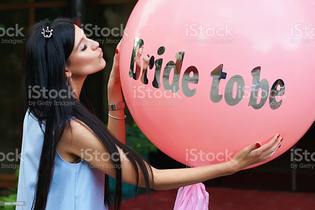 Young beautiful brunette bride to be with dark hair and silver crown on it kissing her pink bachelorette party balloon stock photo