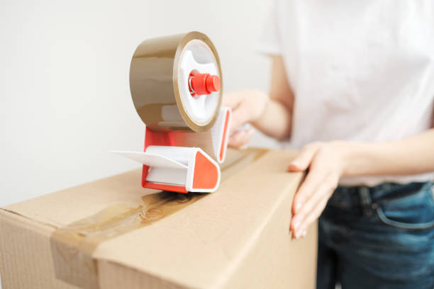 young beautiful brunette girl in a white t-shirt packs cardboard boxes with a dispenser and adhesive scotch adhesive tape. the concept of moving to a new home. - oggetti personali foto e immagini stock
