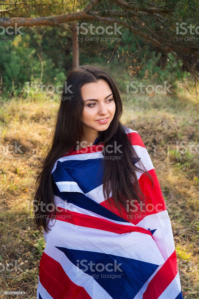 Young beautiful brunette girl posing with  British flag in park photo libre de droits