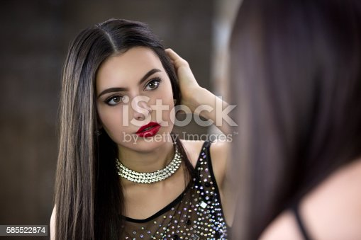 istock Young beautiful brunette looks in the mirror and straightens hair 585522874