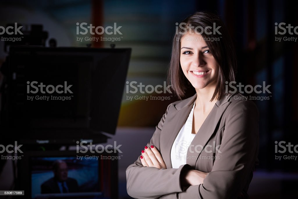 Young beautiful brunette television announcer standing next to the camera stock photo