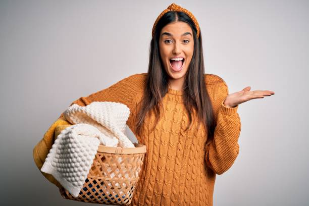 Young beautiful brunette woman doing housework chores holding wicker basket with clothes very happy and excited, winner expression celebrating victory screaming with big smile and raised hands stock photo