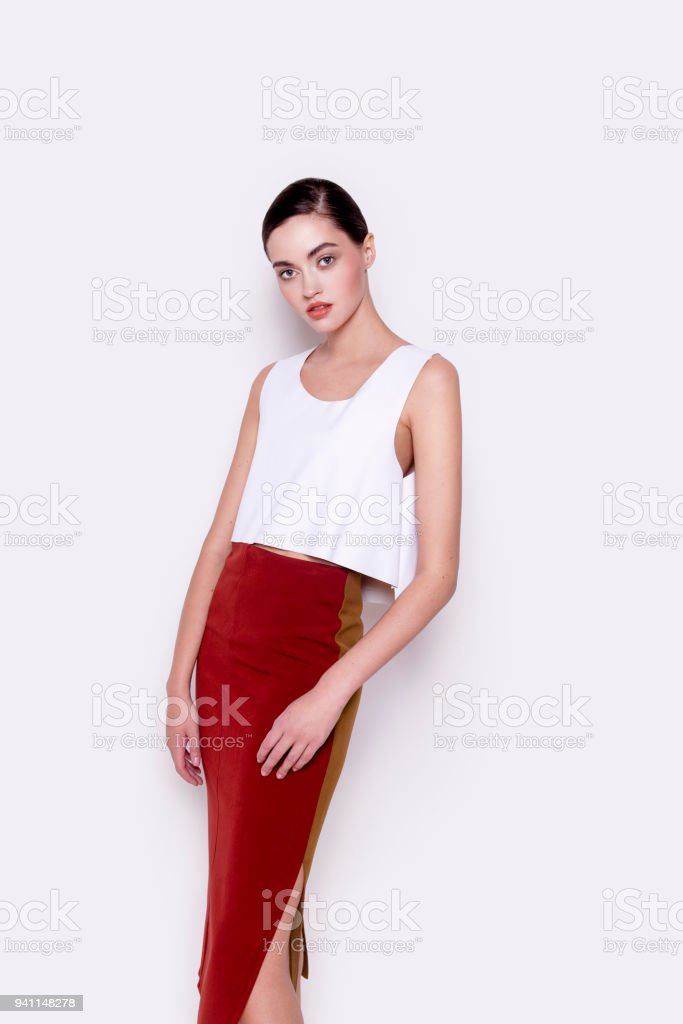 83f4c248a0 Young beautiful brunette woman in trendy clothes white top and red stylish  skirt royalty-free