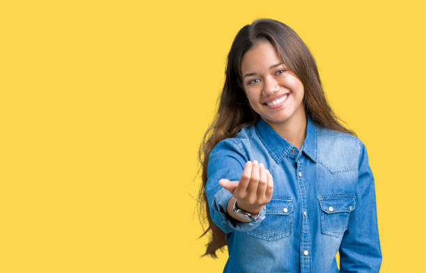 Young beautiful brunette woman wearing blue denim shirt over isolated background Beckoning come here gesture with hand inviting happy and smiling stock photo