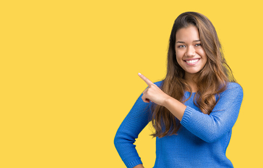 istock Young beautiful brunette woman wearing blue sweater over isolated background Pointing with hand finger to the side showing advertisement, serious and calm face 1098404010