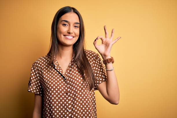Young beautiful brunette woman wearing casual shirt over isolated yellow background smiling positive doing ok sign with hand and fingers. Successful expression. stock photo