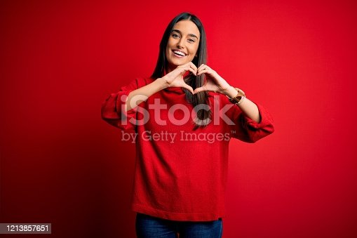 Young beautiful brunette woman wearing casual sweater over isolated red background smiling in love doing heart symbol shape with hands. Romantic concept.