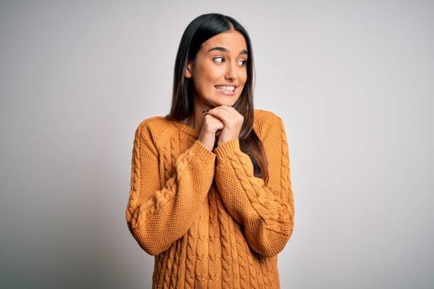 Young beautiful brunette woman wearing casual sweater over isolated white background laughing nervous and excited with hands on chin looking to the side stock photo