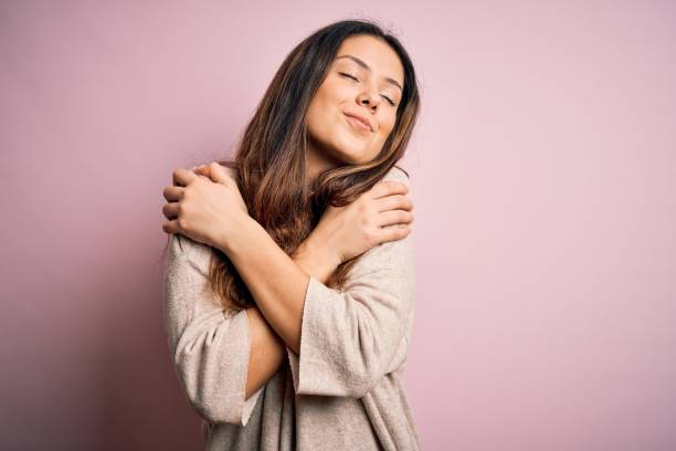 年輕漂亮的黑髮女郎穿著休閒毛衣站在粉紅色的背景上擁抱自己快樂和積極,微笑著自信。自我愛和自我關懷 - 僅一名女人 個照片及圖片檔